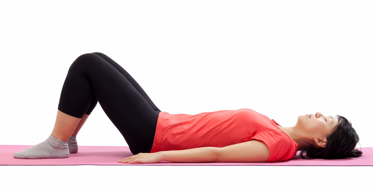 woman-laying-on-mat-with-bent-knees