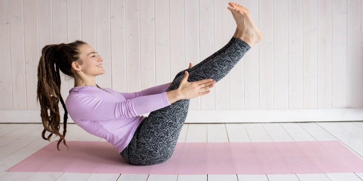 woman-wearing-purple-top-exercising-on-mat