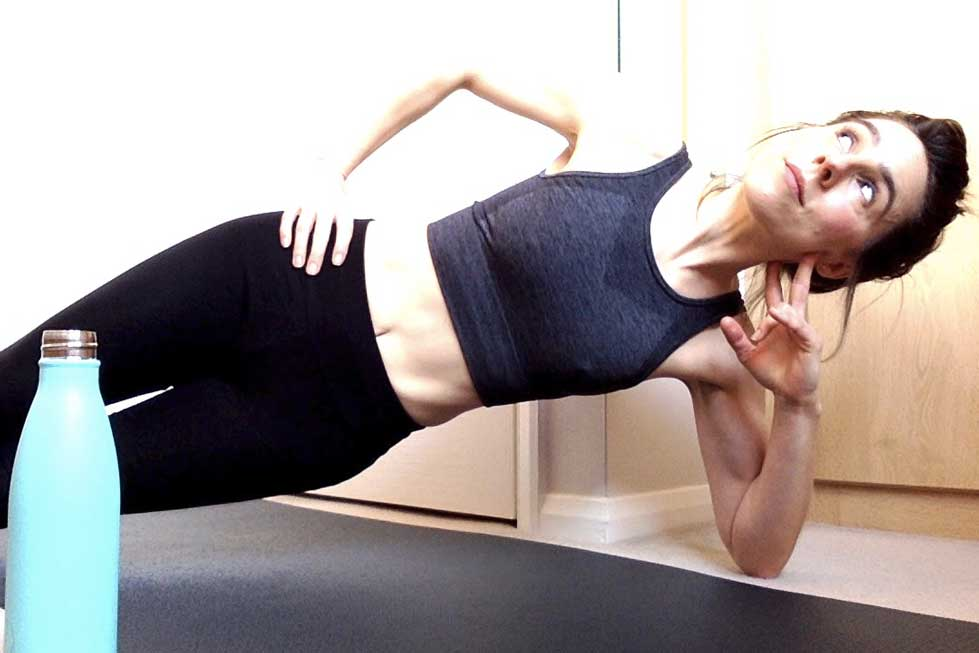 Kathryn Knights doing Pilates side plank with one hand on hip, looking sideways towards the ceiling