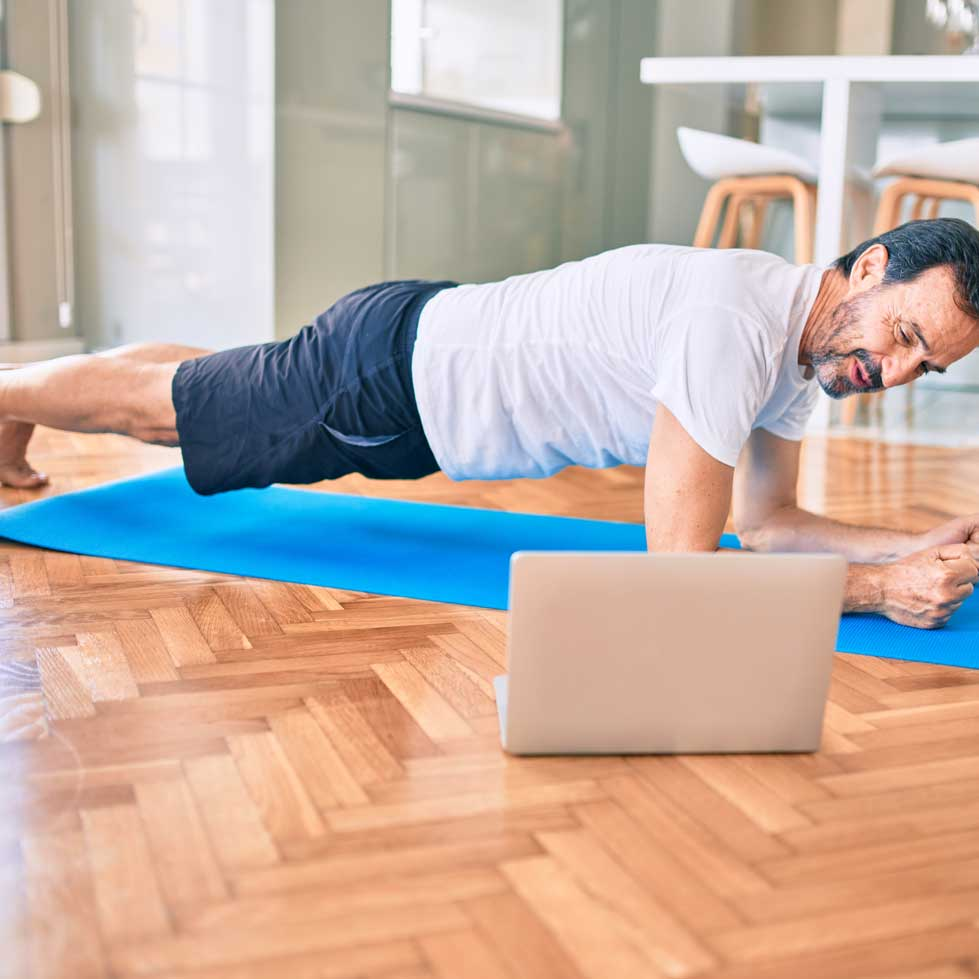 Middle-aged man doing a Saturday morning Zoom Pilates for beginners class, holding plank position on his forearms
