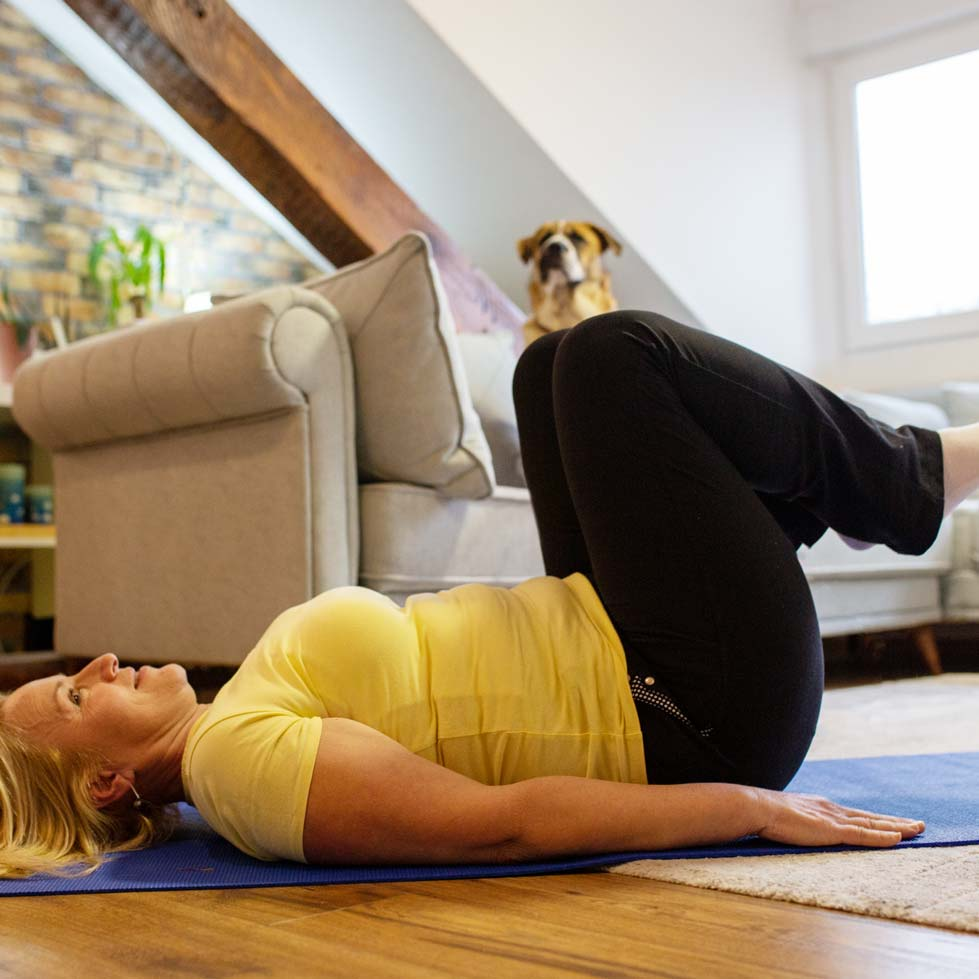 Senior woman doing a beginners' Zoom Pilates class, lying on back with knees lifted to chest