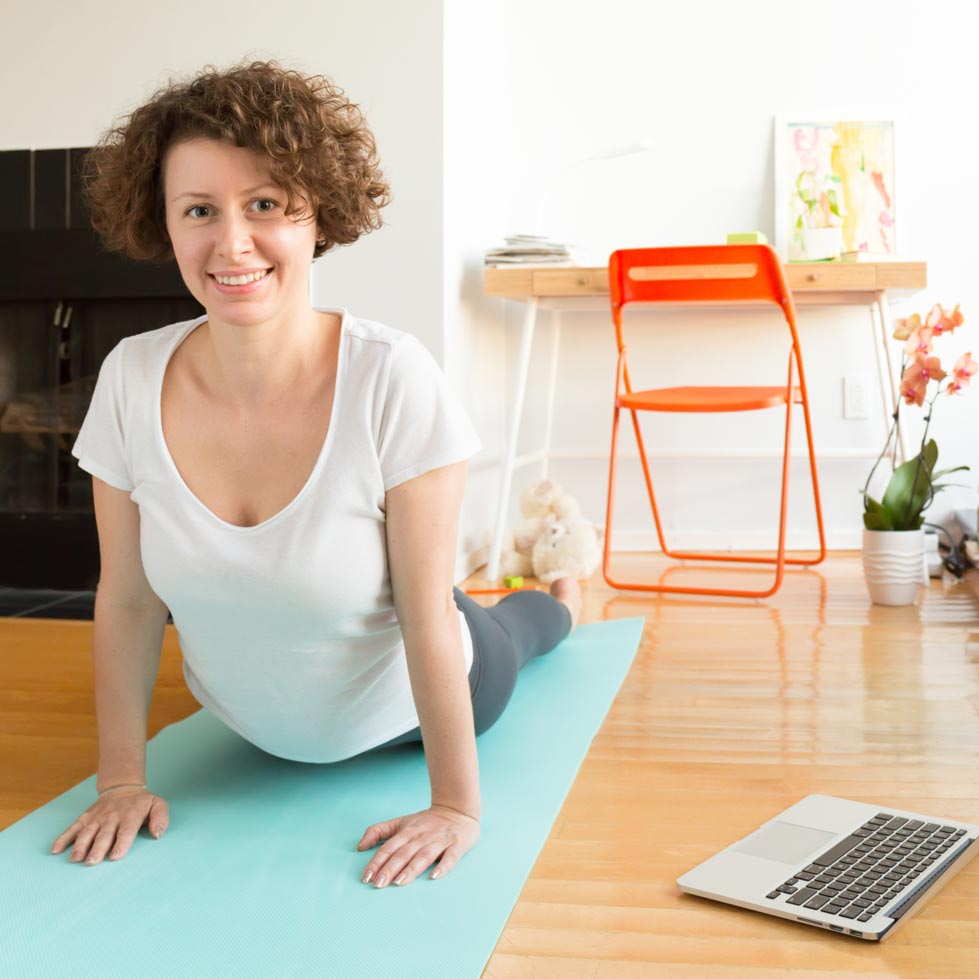 Woman doing an online Pilates at home in the daytime
