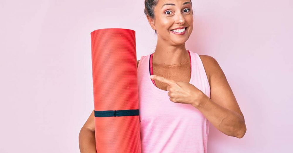 Woman holding Pilates mat, smiling and pointing at it